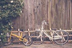 Cyklar som parkerar nära den wood väggen (filtrerad bilden bearbetad tappning Royaltyfri Bild