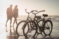 Cyklar som parkerar på kust med par i bakgrund Arkivfoto