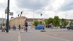 Cykliści czekają zielonego sygnał przy miasta crosswalk i wtedy krzyżują drogę zbiory