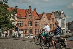 Cykliści i piechur na moscie nad kanałem w Bruges Obrazy Royalty Free