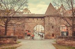 Cykliści jedzie past dziejowych ściana z cegieł Stary miasto z łukiem i wierza Zdjęcie Royalty Free