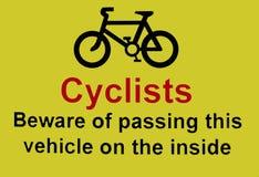 Cykliści one wystrzegają się przechodzić pojazd na wśrodku znaka zdjęcia stock
