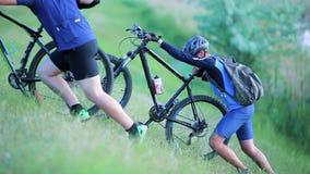 Cykliści pcha rowery up wzgórze zbiory wideo