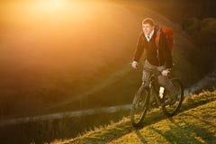 Cyklistów stojaki do następu wzdłuż stromej wspinaczki Cyklisty pedałować ciężki z tłem przy zmierzchem Fotografia Stock
