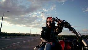 Cyklist för gammal kvinna i ett läderomslag och handskar som sitter på hans motorcykel Där ` s en tom huvudväg i bakgrunden