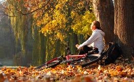 Cyklist för ung kvinna som kopplar av på den utomhus- soliga hösten Arkivbild