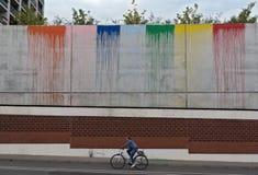 Cyklist framme av den kulöra betongväggen Arkivbilder