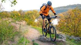 Cyklist i apelsin som rider mountainbiket på Autumn Rocky Trail Extrem sport och Enduro som cyklar begrepp
