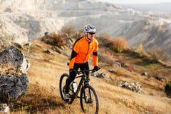 Cyklist i orange omslag som rider cykeln Rocky Hill Extremt sportbegrepp Utrymme för text royaltyfri bild