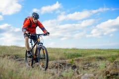 Cyklist i röd omslagsridningmountainbike på den härliga våren Rocky Trail Extremt sportbegrepp royaltyfria bilder
