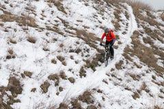 Cyklist i röd ridningmountainbike på den snöig slingan Extrem vintersport och Enduro som cyklar begrepp Fotografering för Bildbyråer