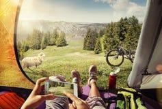 Cyklist i tältet med mobilen Arkivfoton