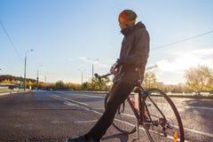 Cyklist med cykeln på en tom stadsgata Royaltyfria Foton