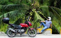 Cyklist med en motorcykel som vilar under en palmträd med kokosnötter royaltyfria bilder