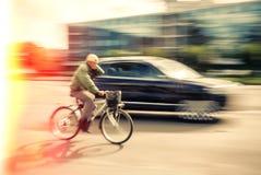 Cyklist och en bil på gatan Fotografering för Bildbyråer