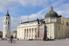 Cyklist på en fyrkant med domkyrkabasilikan och Klocka torn i Vilnius, Litauen Arkivbild
