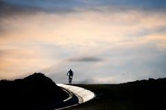 Cyklist på en väg Fotografering för Bildbyråer