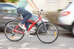 Cyklist på hastighet längs den stads- gatan Arkivfoton