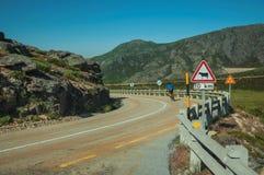 Cyklist på vägen som passerar till och med stenigt landskap arkivbild