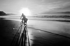 Cyklist som cyklar på stranden på solnedgången med cykelskugga Royaltyfria Bilder