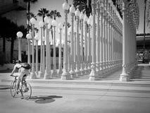 Cyklist som framme poserar av stads- ljus på LACMA Fotografering för Bildbyråer