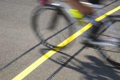 Cyklist som når mållinjen som konkurrerar på ett lopp Arkivfoto