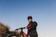 Cyklist som ner rider cykeln Rocky Hill p? solnedg?ngen Extremt sportbegrepp arkivfoton