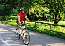 Cyklist som rider en cykel i parkera arkivbild