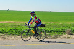 Cyklist som rider en cykel på en öppen väg Arkivfoton