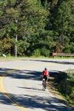cyklist som rider ner vägspolning Arkivfoton