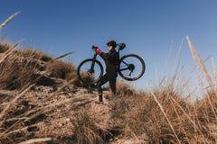 Cyklist som rymmer cykeln ner Rocky Hill p? solnedg?ngen Extremt sportbegrepp royaltyfria foton