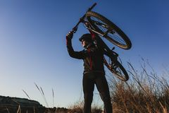 Cyklist som rymmer cykeln ner Rocky Hill p? solnedg?ngen Extremt sportbegrepp arkivfoton