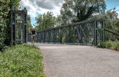 Cyklist som ses korsa en bro i sommartid Royaltyfria Bilder
