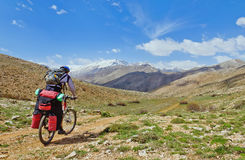 Cyklist som springer på bergslinga Arkivfoto