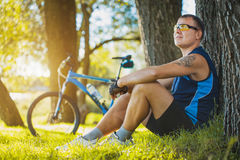 Cyklista odpoczywa pod drzewem Zdjęcia Stock
