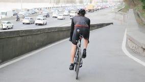 Cyklista pochodzi w kierunku ruchliwie miasto drogi jest ubranym czarnego sportswear Kolarstwa poj?cie swobodny ruch zbiory