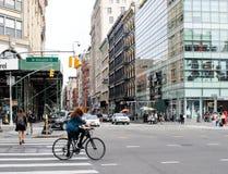 Cyklista robi jej sposobowi wzdłuż W Houston St w w centrum Manhattan Fotografia Stock