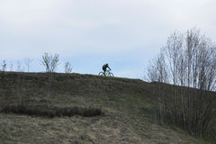 Cyklista rusza się na górze wzgórza równego horyzont fotografia stock