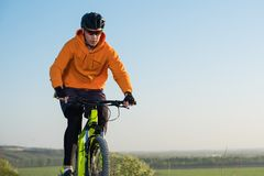 Cyklista w pomarańczowym hoodie jedzie rower wzdłuż halnej ścieżki Pojęcie krańcowi sporty obrazy royalty free