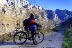 Cyklista z jego rowerem górskim wskazuje jego rękę przy kierunkiem trasa obraz royalty free