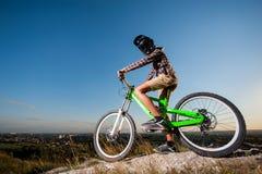 Cyklista z rowerem górskim na wzgórzu pod niebieskim niebem fotografia royalty free
