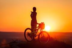 Cyklista z rowerem górskim na wzgórzu w wieczór Fotografia Stock