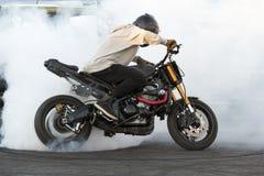 Cyklistbränninggummihjul och skaparök på cykeln i rörelse arkivfoto