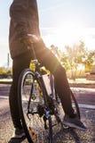 Cyklisten är den stående near vägcykeln Arkivbild