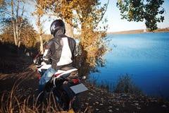 Cyklisten ankom på en motorcykel till sjön utrustning hjälm handskar royaltyfri foto