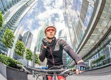 Cyklisten för den unga mannen rider på cykeln på gatan bland skyskrapor fotografering för bildbyråer