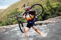 cyklisten går berg över floden Royaltyfri Fotografi