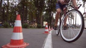Cyklisten går runda trafikkottar Ung stilig man som rider en tappningcykel Sportig grabb som cyklar på parkera Sunt Royaltyfria Foton