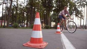 Cyklisten går runda trafikkottar Ung stilig man som rider en tappningcykel Sportig grabb som cyklar på parkera Sunt Fotografering för Bildbyråer
