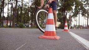 Cyklisten går runda trafikkottar Ung stilig man som rider en tappningcykel Sportig grabb som cyklar på parkera Sunt Arkivfoto